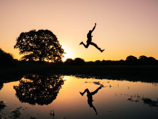 夕方水辺でジャンプルする人